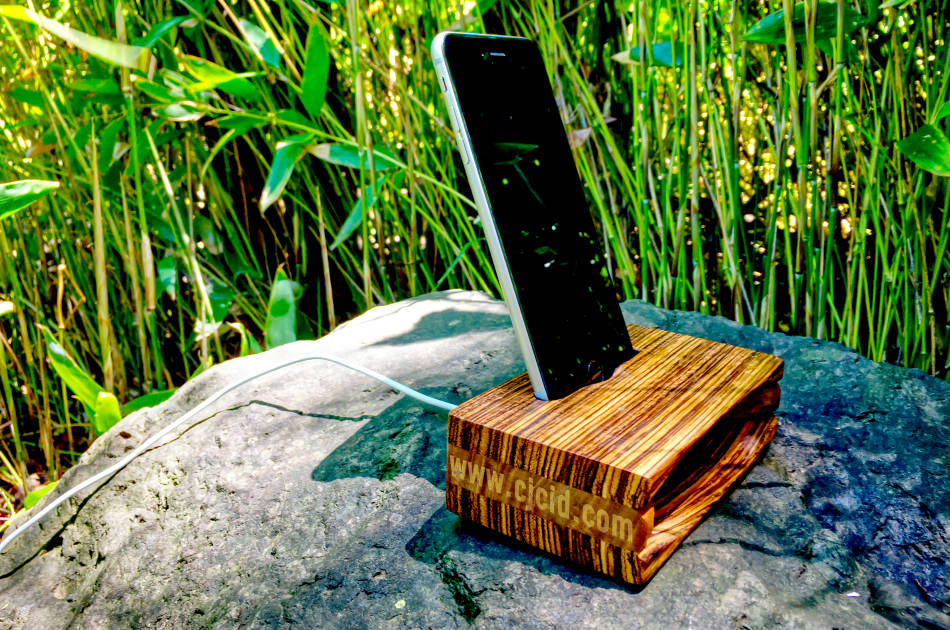 "Side view of the handmade wooden iPhone stand and passive amplifier speaker ""CJ Monster Mouth"" with an iPhone and charging cable attached"